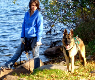 Person and German Shepherd by the lake